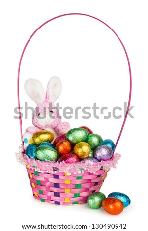 A Toy Bunny and Colorful Basket full of Chocolate Easter Eggs - stock photo