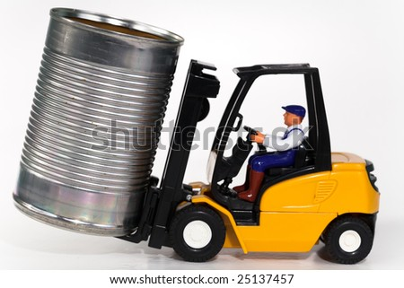 A toy forklift truck lifting a tin can. - stock photo
