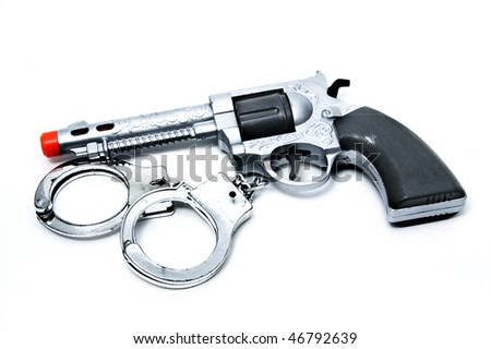 a toy gun and handcuffs isolated on a white background - stock photo