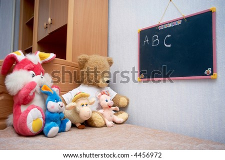 A toys sitting at the blackboard - stock photo
