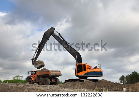 a Track excavator machine loading dumper truck with soil in front of a cloudy sky - stock photo