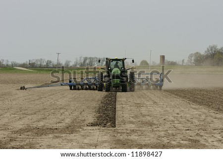 a tractor and planter working in a field - stock photo