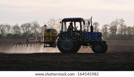 A tractor is in the field - stock photo