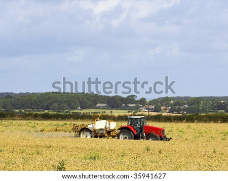 a tractor mounted crop sprayer in action in a wheatfield - stock photo