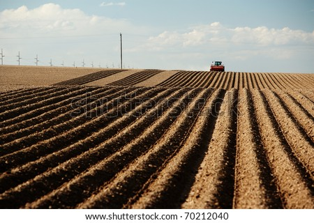 A tractor planting a farm field in the spring. - stock photo