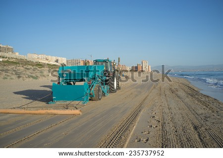 A tractor with a trailer cleaning a beach in the early hours of the morning - stock photo