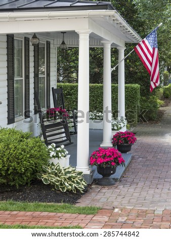 A traditional American home with a white picket fence and flag waving in a small town. - stock photo