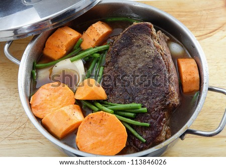 A traditional American pot-roast with beef, gravy, onion, sweet potato and green beans. This is at the cooking stage where the vegetables have just been added - stock photo