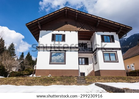 a traditional big austrian house in winter with a vibrant blue sky - stock photo