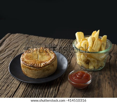 A Traditional British meat pie and chips sitting on a rustic wooden table. - stock photo