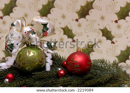 A traditional christmas decoration, christmas ball with christmas bow tied to it, pine branch, copy space, mistletoe background and merry christmas written on it - stock photo