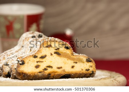A  traditional christmas stollen with a cup and a christmas ball in front of a wooden background