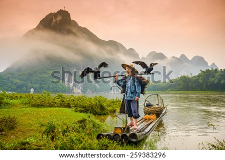 A traditional cormorant fisherman works on the Li River Yangshuo, China. - stock photo