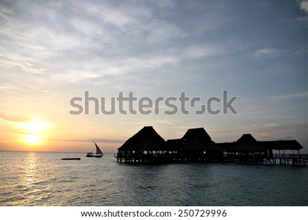 A traditional dhow cruises past a beautiful resort in Zanzibar as the sun sinks towards the horizon.  - stock photo