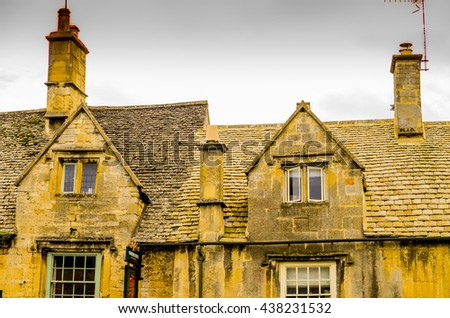 a traditional english cotswold village with old houses - stock photo