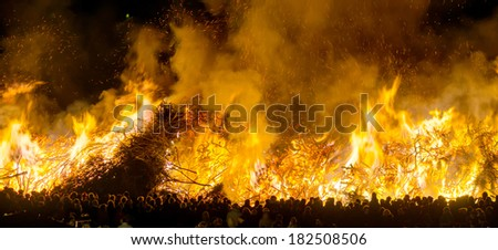 A traditional festival called Biikebrennen in North Frisian, Germany showing a huge fire and some spectators watching the ceremony. - stock photo