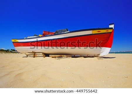 A traditional fishing boat moored on Meia Praia beach near Lagos,The Algarve, Portugal - stock photo