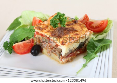 A traditional Greek moussaka, made with layers of potato, aubergine, meat, and tomato sauce, topped with bechamel sauce and served with salad. - stock photo