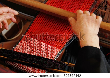 A traditional hand-weaving loom being used to make cloth  - stock photo