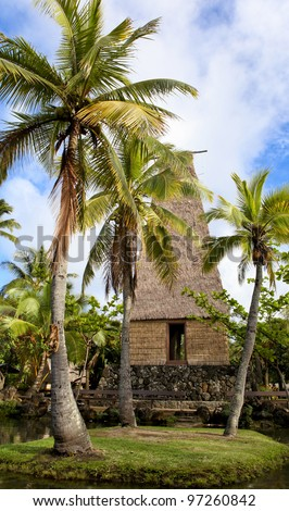 A traditional Hawaiian hut and palm trees in Polynesian Cultural Center Oahu Hawaii - stock photo