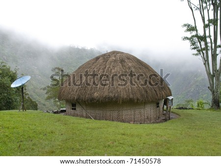 A traditional hut and satellite dish in an mountain village. New Guinea - stock photo