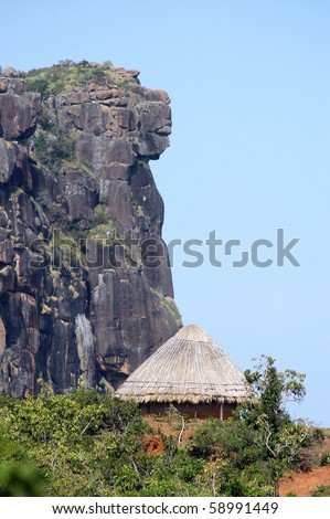 A traditional hut below the dame de mali rock formation in fouta djalon mountains in Guinea - stock photo