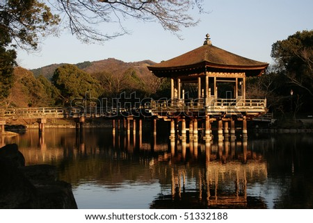 A traditional Japanese pavilion in park settings at Nara, Japan's first capital. It's a great place to relax and enjoy the sunset. - stock photo