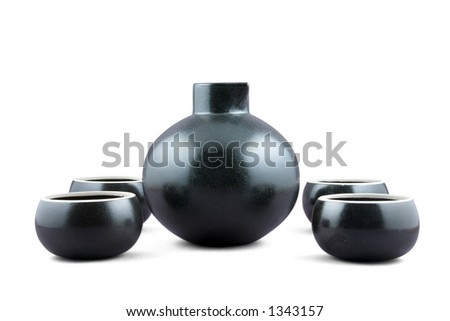 A traditional Japanese style Sake set comprising a jug and four bowl cups. Isolated with path. - stock photo