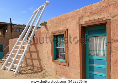A traditional kiva ladder rests against an adobe building at the Acoma Pueblo in New Mexico. - stock photo