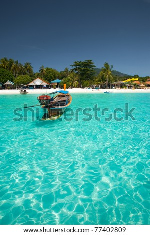 A traditional longtail boat floats in perfect crystal clear emerald blue water on the island paradise of Koh Lipe (aka Ko Lipeh), Thailand - stock photo