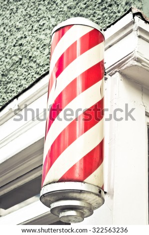 A traditional red and white cylinder outside a barber's shop - stock photo