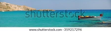 A traditional small Greek Fishing Boat moored in Crystal Blue Water off Manganari Beach, Ios Island, Greece. - stock photo