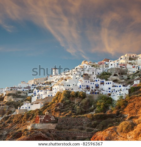 A traditional view of the windmills of Oia near to the time of sunset on the greek paradise island of Santorini.