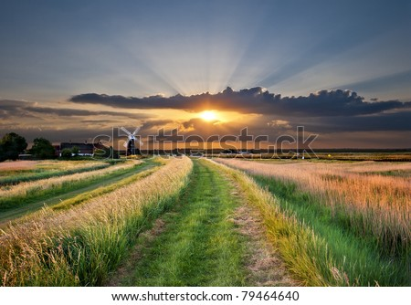 a traditional windmill pump on the Bure marshes of the norfolk broads in england, uk, with a beautiful, spectacular sunset in the background - stock photo