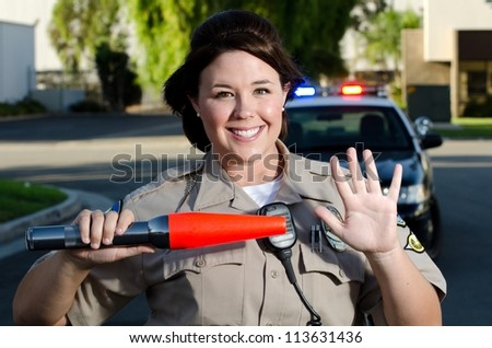 a traffic cop gives traffic a stop hand gesture while holding her flashlight. - stock photo