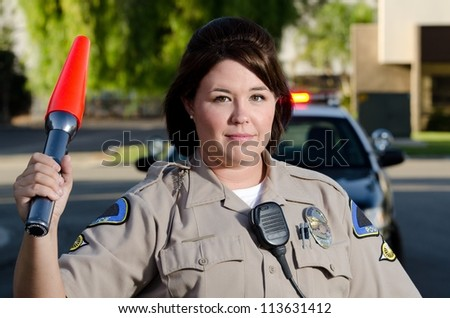 a traffic cop waves her flashlight to get cars to go.