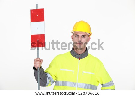 A traffic guard holding up a sign - stock photo