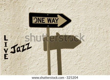 A traffic one-way sign and a Live Jazz sign painted on the wall. - stock photo