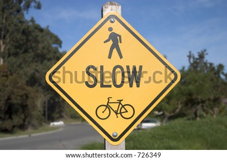 A traffic sign warns cars to slow down and look for bikers and pedestrians.