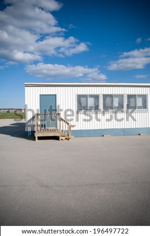 A trailer and a field under a cloudy blue sky. - stock photo