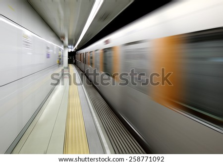 A train zooming at high velocity through an underground train station. - stock photo