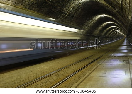 A tram disappearing into a tunnel - stock photo