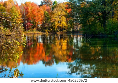A tranquil pond reflects the colors of a late afternoon in autumn - stock photo