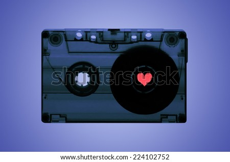 A transparent cassette tape on a purple back-lit background with a pink heart shaped spool on the right hand side