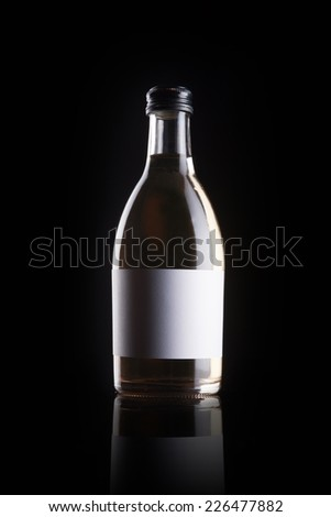 A transparent glass bottle with liquor with blank label reflective bottom isolated black.