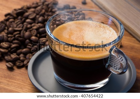 A transparent glass cup of hot steamy espresso on a saucer standing on a wooden table top, surrounded by coffee beans and a vintage book - stock photo