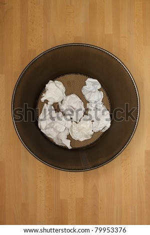 A trash bin isolated on a wooden floor - stock photo