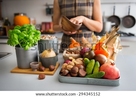 A tray full of Autumn fruits, nuts, and vegetables sits on a kitchen counter. Next to the tray, a wooden cutting board featuring a fresh basil plant and onion promise a delicious meal ahead. - stock photo