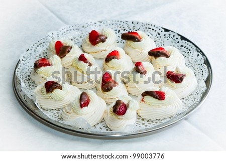 A tray of cakes and meringues with strawberries in chocolate. Against the background of a white tablecloth. - stock photo