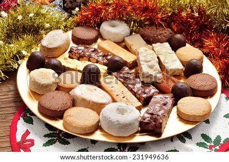 a tray with different turron, polvorones and mantecados, typical christmas confections in Spain, on an ornamented table - stock photo